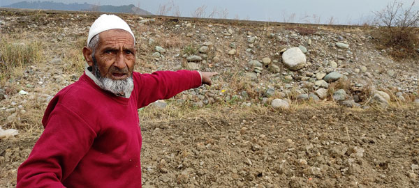 Munawar-Wani-pointing-towards-the-road-which-was-built-over-his-agricultural-land-by-the-government-few-years-back